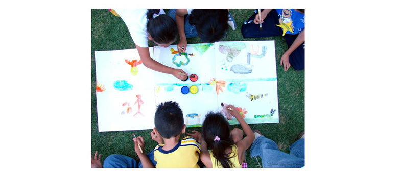 A group of children drawing pictures on a large sheet of paper.