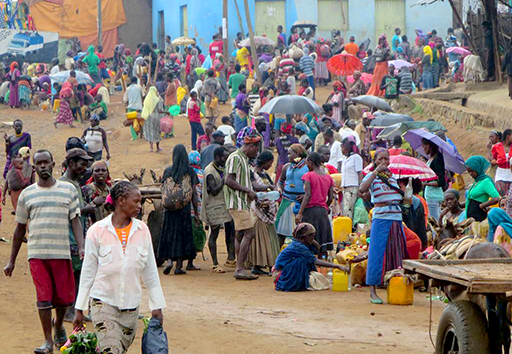 Crowd of people at an African market some with water carriers