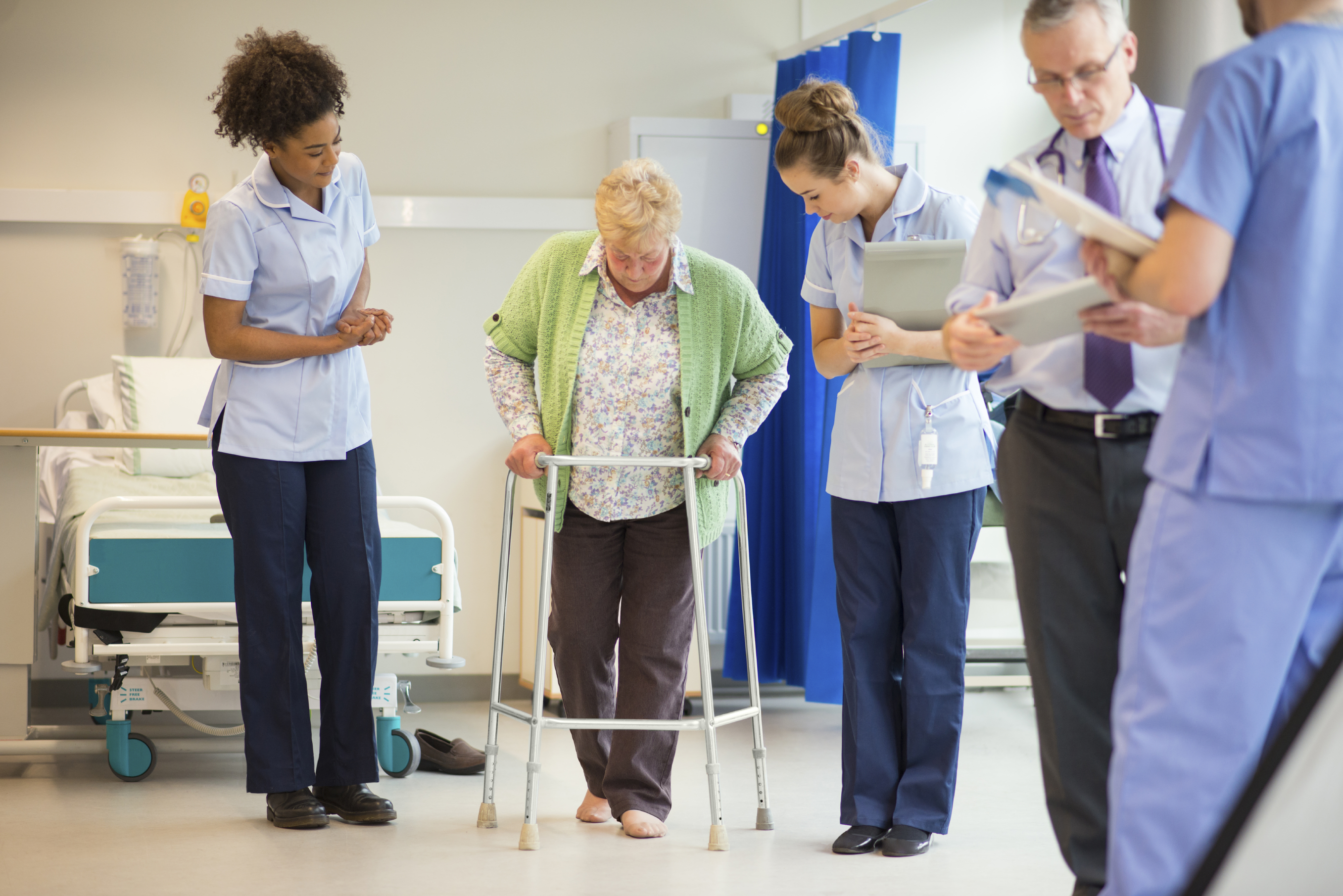 This photo shows a senior patient using a walking frame on a hospital ward, supported by her health care team.