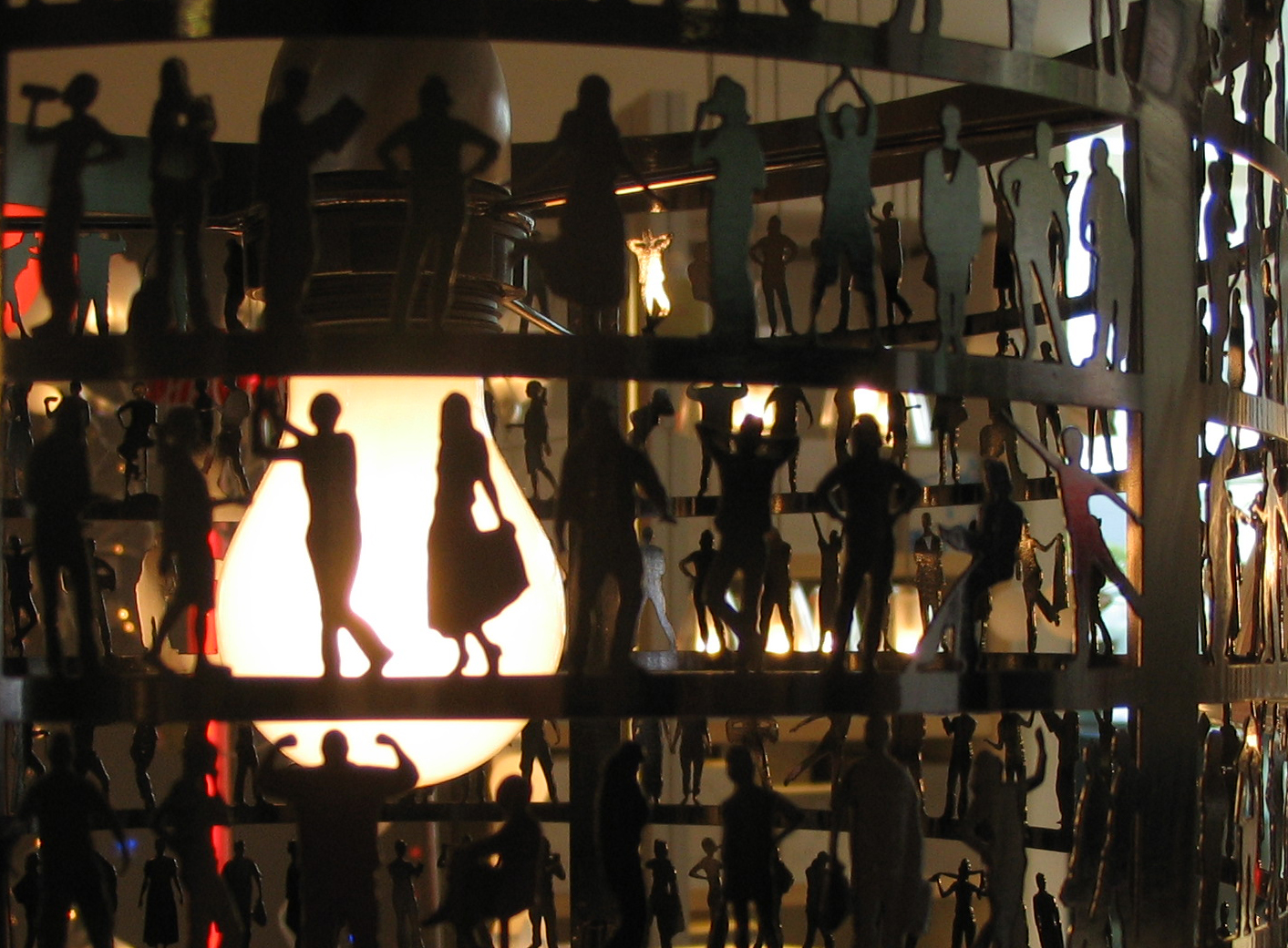 Lamp with silhouettes of people doing different activities all around it