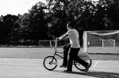 Black and white photo of a man helping a child ride a bike
