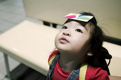 Little girl looking up very still and holding a piece of paper on her forehead