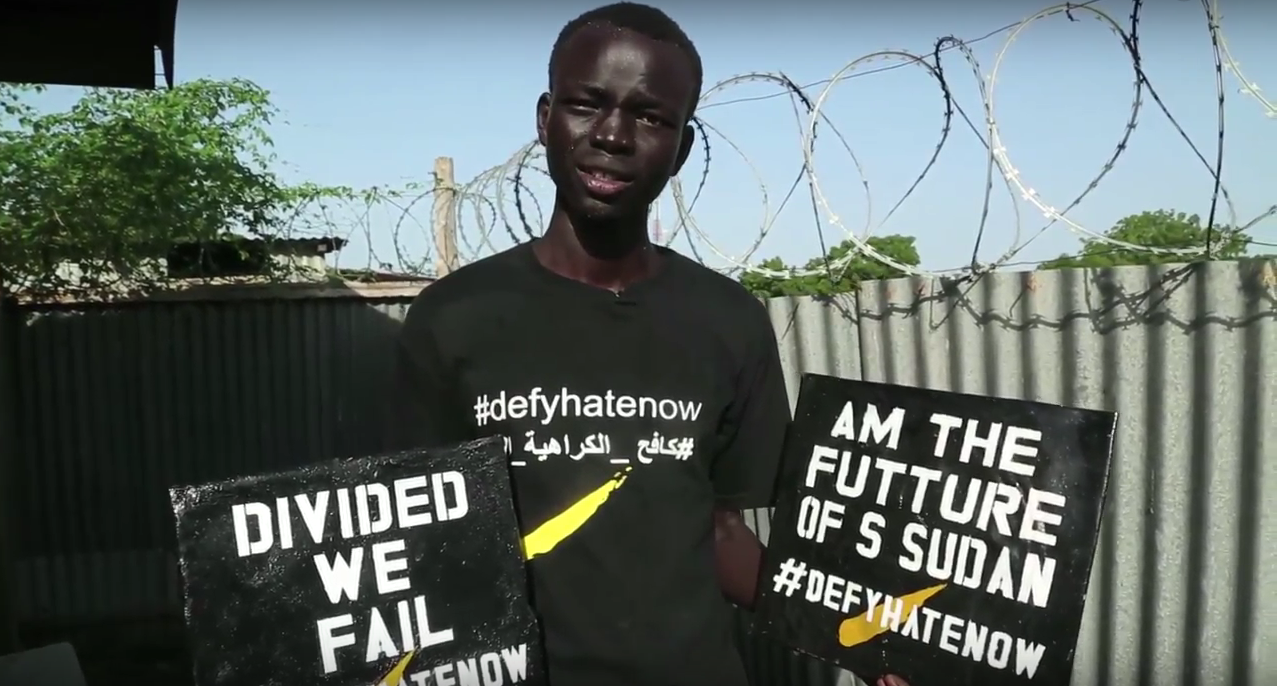 Bior Ajang with #defyhatenow signs made by high school students in Bor, South Sudan