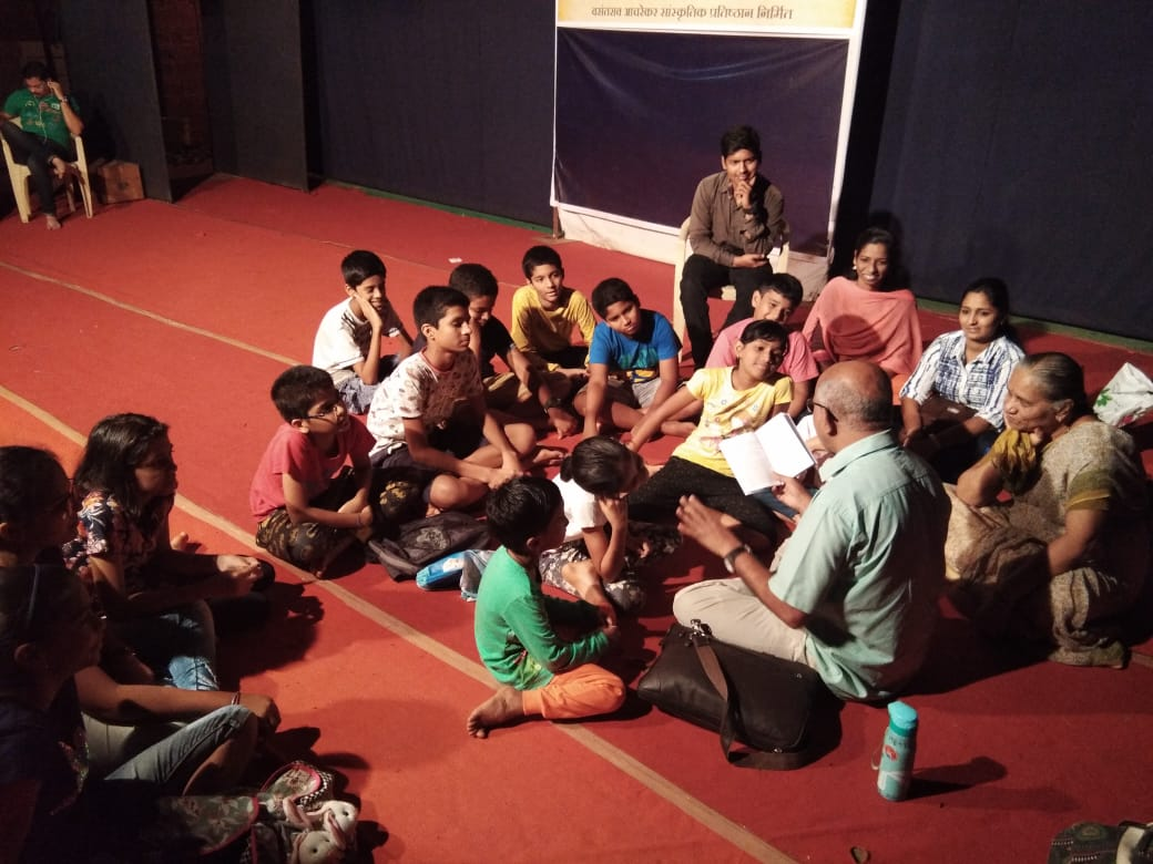 Children and some adults around a teacher, reading from a book, preparing for theater