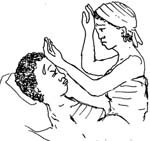 A woman is lying in a bed with sweat dripping off her forehead. A health worker is seated on the bed beside her. She has the back of one hand placed on the woman's head and the back of the other hand on her own head.