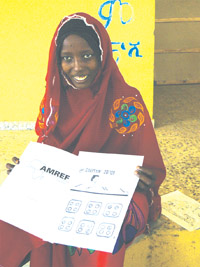 A health worker shows a chart with Coartem tablets in groups of four.