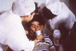 A man with cholera is helped to drink oral rehydration salts