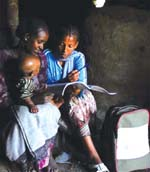 A mother receives health education from a HEP whilst a small child sits on her knee.