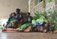 Children seated on a bench outside their classroom. Beside them is a pile of vegetable.