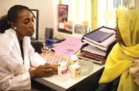 A healthcare worker discusses medication with a patient whilst seated in her office.