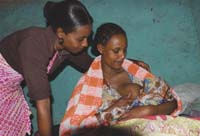 A healthcare worker counsels a mother on correct breastfeeding techniques whilst the mother is breastfeeding.