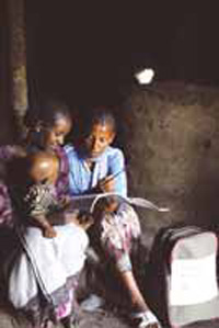 A health worker visits a mother at home. She shows her illustrated leaflets. A baby sits on the mothers knee.