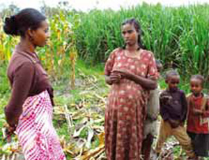 A community health worker talks to a pregnant woman amongst crops. Standing behind the pregnant woman stand three children.