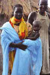 A woman standing outside her home. She is holding her baby and has an insecticide-treated net wrapped around her.