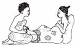 A pregnant woman is receiving a foot massage from another woman.