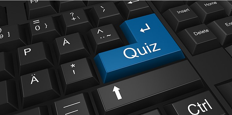 Black computer keyboard with the return key in blue with the word quiz displayed on it in white