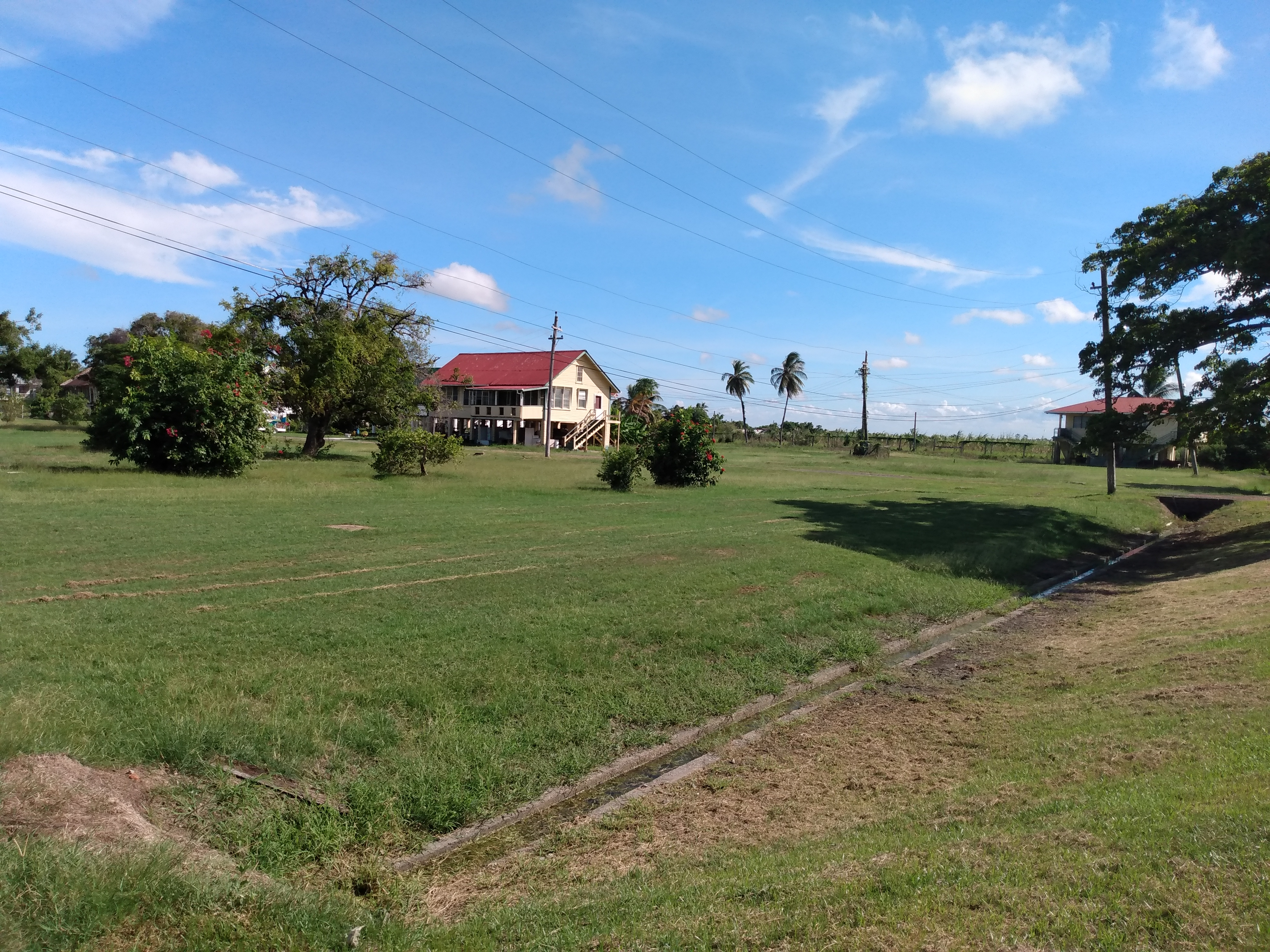 Large grass field with a building in the sunshine showing Enmore.