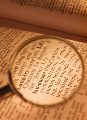"""A magnifying glass over the word """"language"""" with its meaning from a dictionary"""
