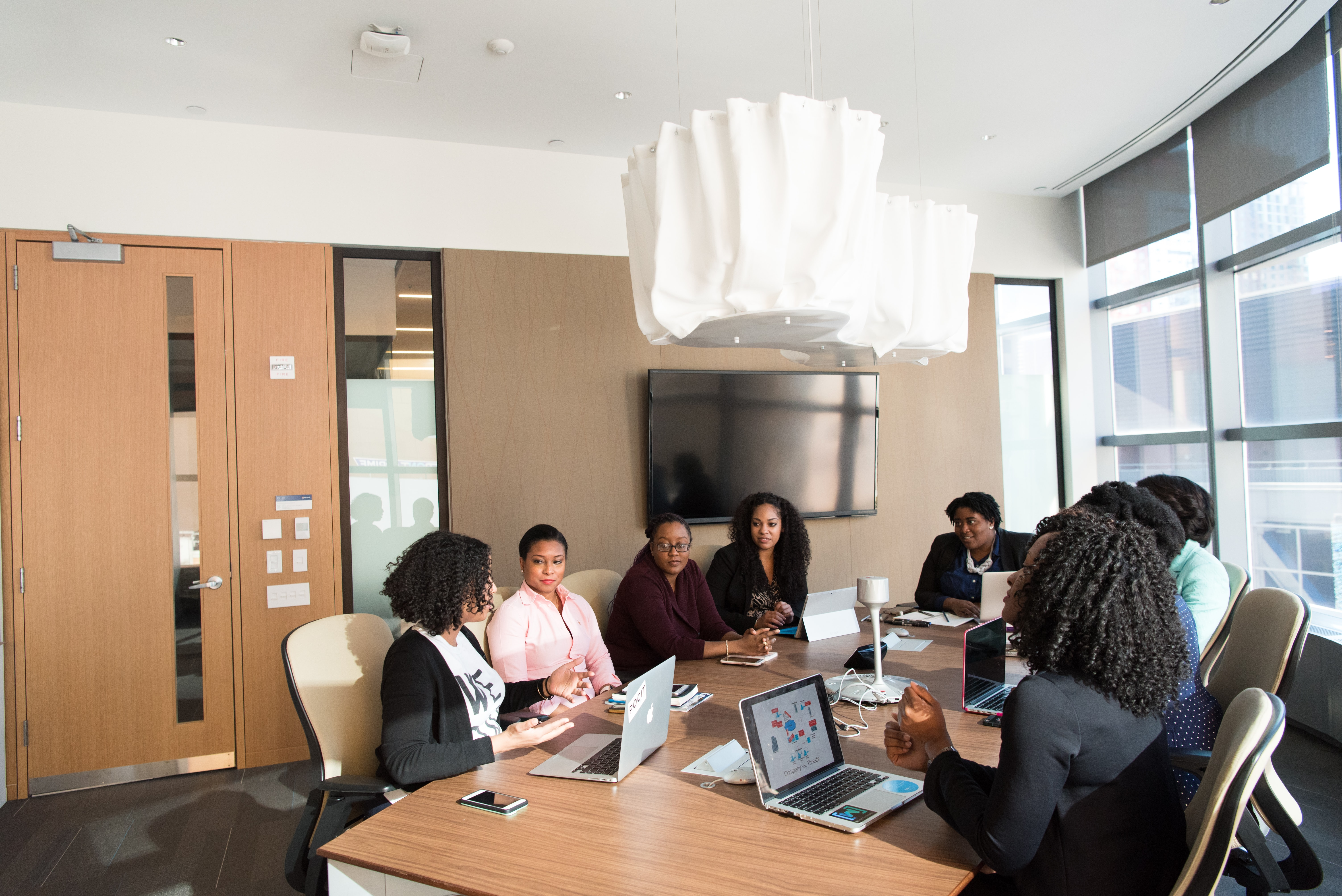 Black colleagues in a meeting room having a conversation.