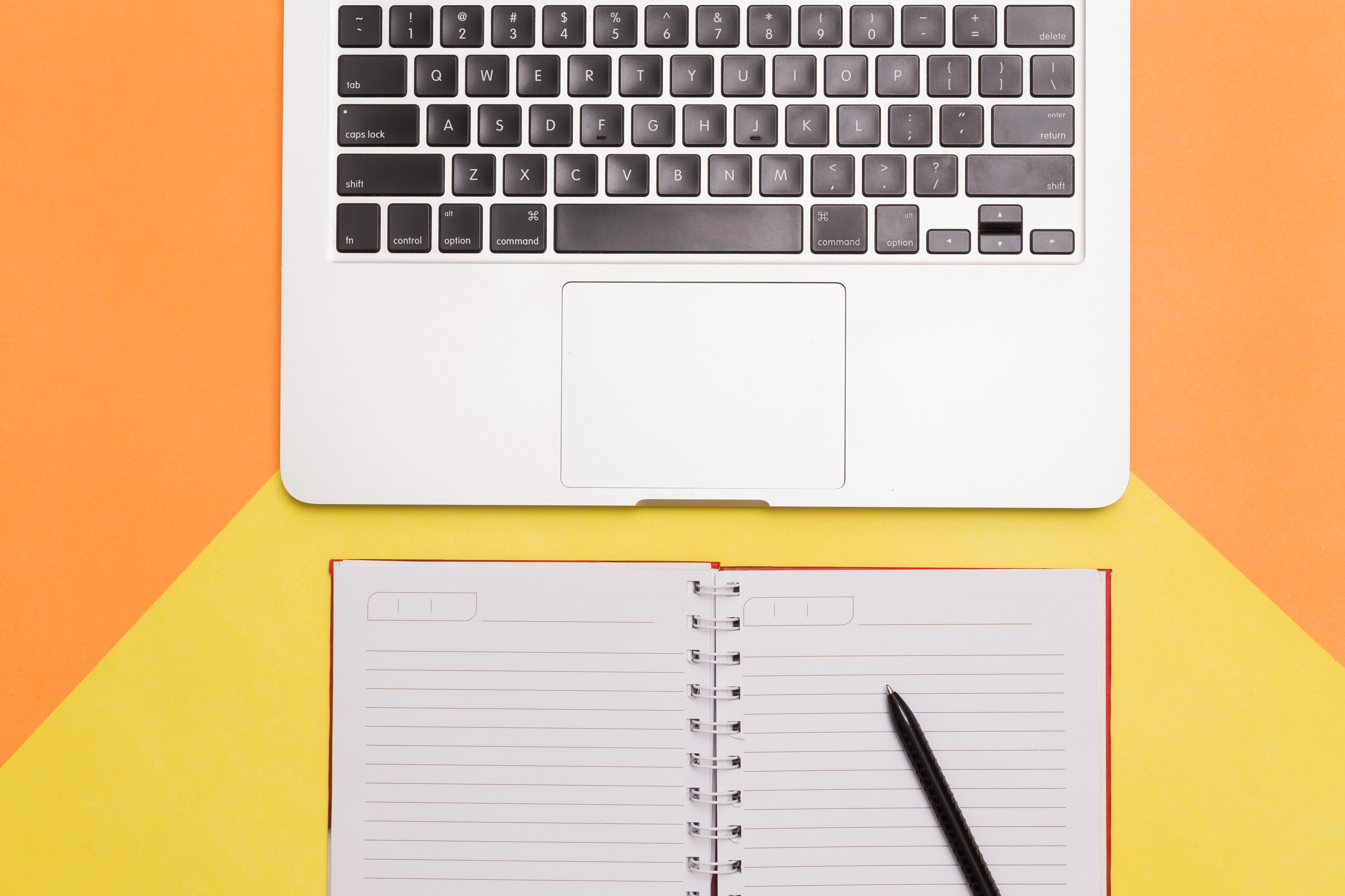 a computer and a blank notebook