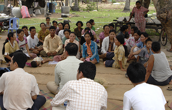 A group of people from a village in Cambodia sat on the floor having a meeting