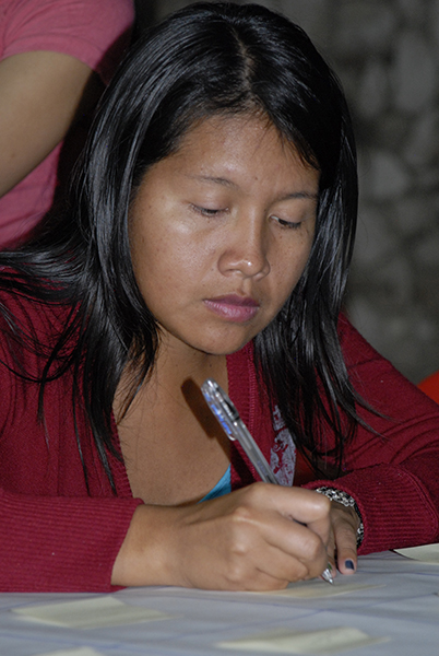 A person writing on a piece of paper with a pen