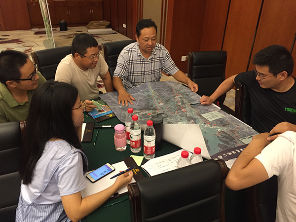 People sat round a table planning how to undertake environmental monitoring