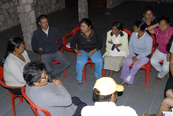 A photo of community members sat on red chairs in a circle discussing the results of environmental monitoring